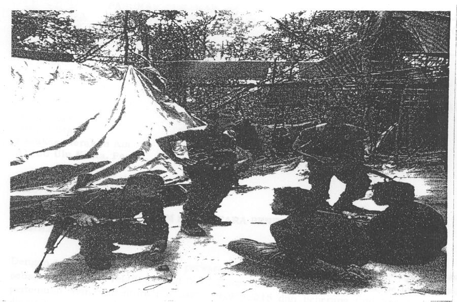 The raiding team with foreign men in custody at the camp where the first mass graves were found.