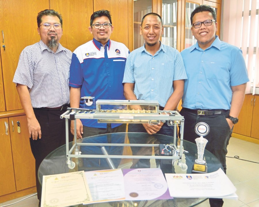 (From left) Universiti Teknologi Mara's Faculty of Electrical Engineering deputy dean Dr Syahrul Afzal Che Abdullah, senior lecturers Dr Noorfadzli Abdul Razak, Dr Fadhlan Hafizhelmi Kamaru Zaman and Dr Mohd Faizul Mohd Idros with a prototype of the automated 'akok' cakes bakery system.