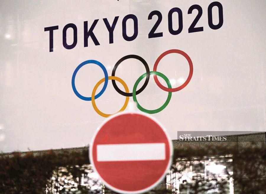 A banner for the upcoming Tokyo 2020 Olympics is seen behind a traffic sign in Tokyo on Monday. - Pix: Reuters