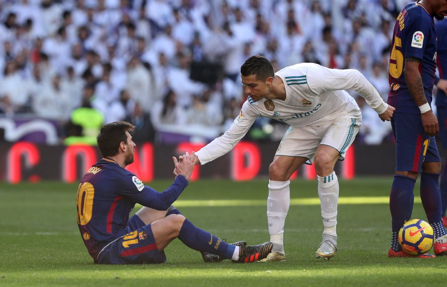 b6b05b29d42 Real Madrid s Cristiano Ronaldo helps Barcelona s Lionel Messi get back to  his feet. REUTERS