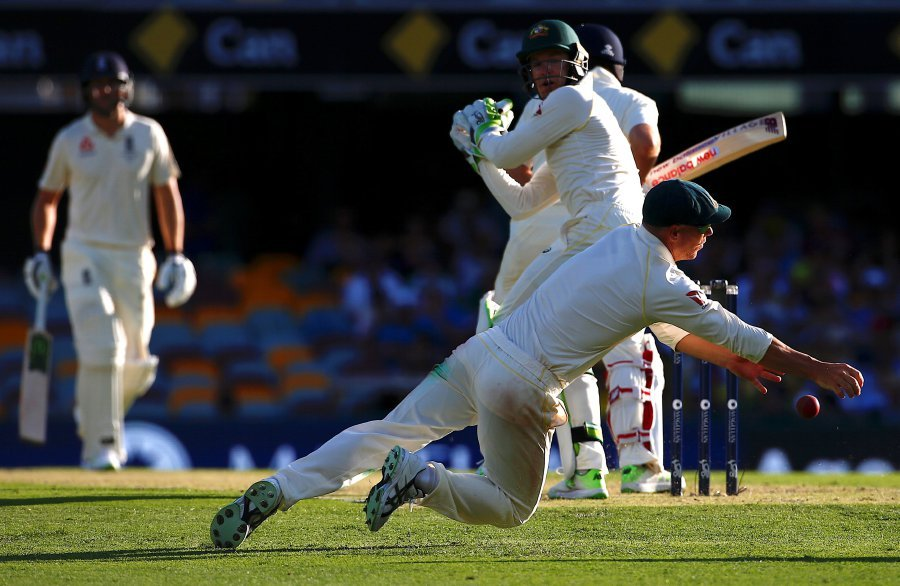 Australia's David Warner dives to stop the ball during the first day of the first Ashes cricket test match. REUTERS