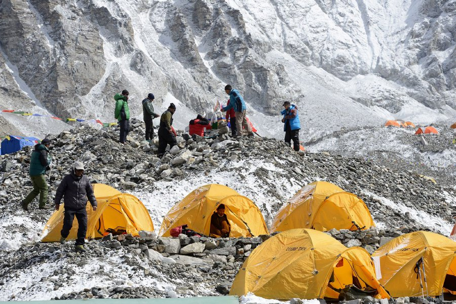 In this photograph taken on April 25, 2018, Sherpa guides (top) prepare for a ritual to pay respects to Mount Everest before beginning their climb, as other climbers look on by their tents at Everest base camp, some 140 kilometres northeast of Kathmandu.Wifi, baked goods and trendy coffee: gone are the days of deprivation at Everest base camp, with hipster perks and modern conveniences ensuring life is cushier than ever on the roof of the world. AFP PHOTO