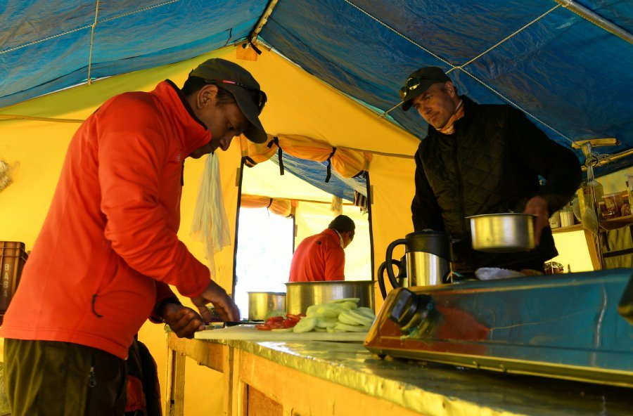 In this photograph taken on April 25, 2018, James Perry (R), a chef at New Zealand-based Adventure Consultants, cooks food in a tent kitchen at Everest base camp, some 140 kilometres northeast of Kathmandu.Wifi, baked goods and trendy coffee: gone are the days of deprivation at Everest base camp, with hipster perks and modern conveniences ensuring life is cushier than ever on the roof of the world. AFP PHOTO