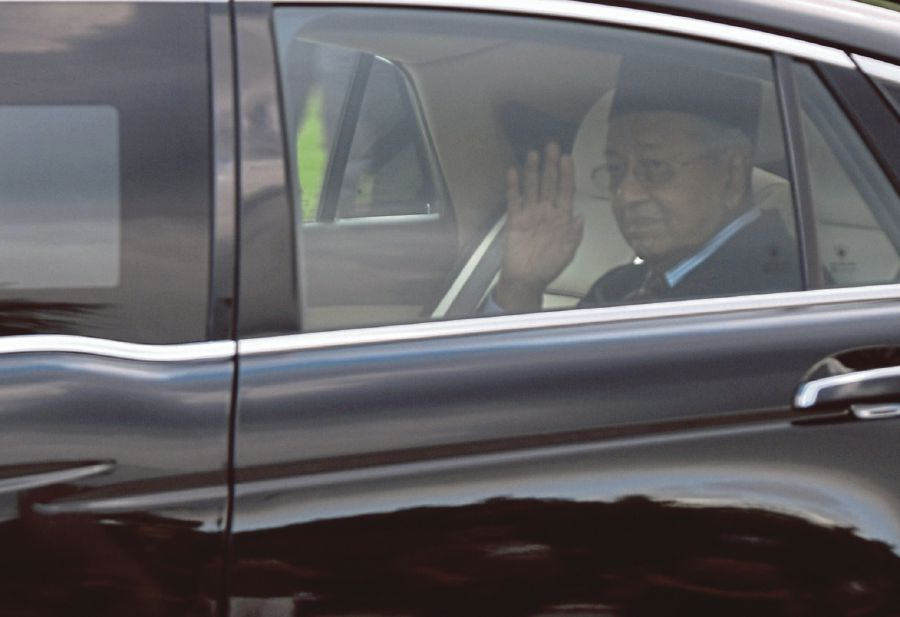 Tun Dr Mahathir Mohamad waving to the media after his meeting with the King at the Istana Negara. - BERNAMA