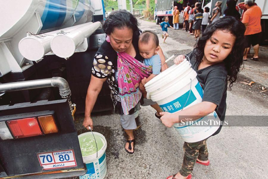Residents collecting water from a water tanker in Seri Kembangan yesterday.NSTP/HAFIZ SOHAIMI
