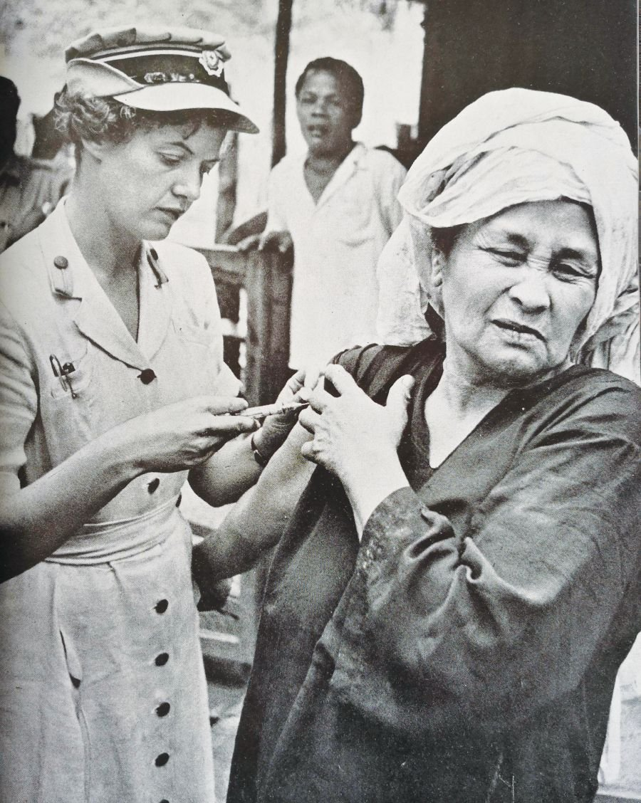 A nurse vaccinating a midwife to prevent the spread of disease to mothers and infants.