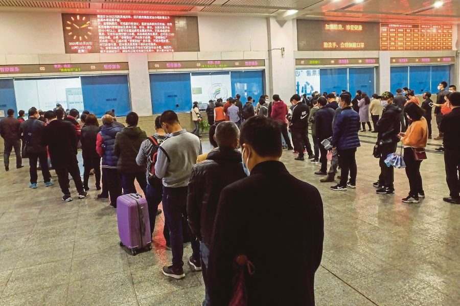 People queueing up to buy train tickets at Yichang East Railway Station in Yichang in China's central Hubei province yesterday. -AFP pic
