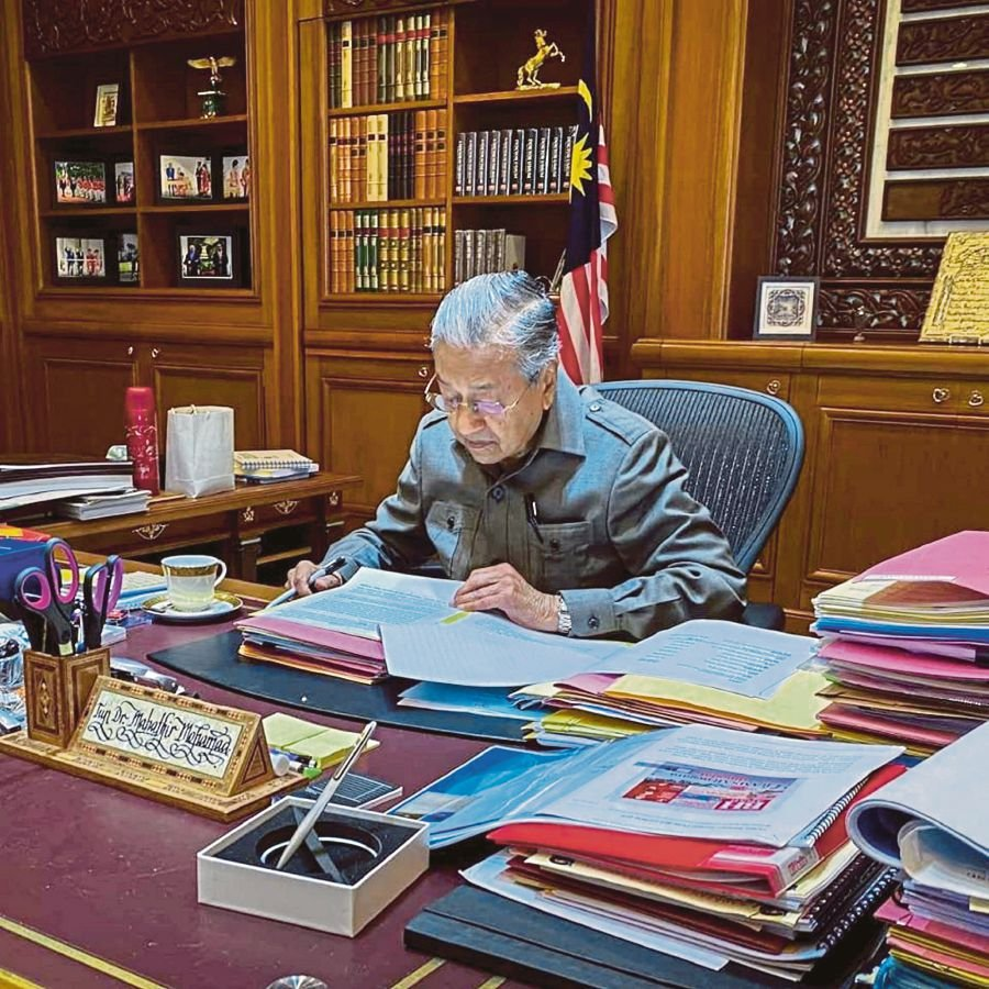 Tun Dr Mahathir Mohamad, who was appointed as interim prime minister on Monday, going through files at his office in Putrajaya yesterday. -Pic taken from Tun Dr Mahathir Mohamad's Facebook page.