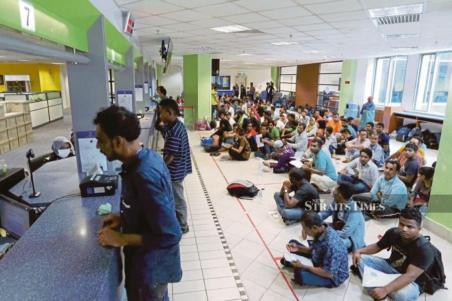 Illegal immigrants queuing at the Immigration Department to apply to join the 'Back For Good' repatriation programme in Putrajaya yesterday. PIC BY AHMAD IRHAM MOHD NOOR