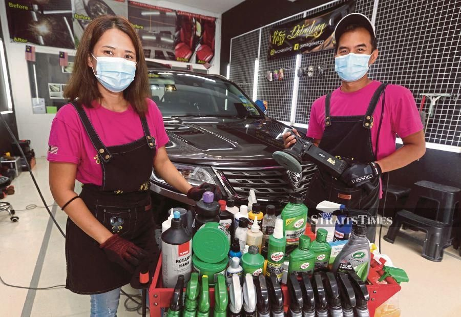 Nazira Azenan (left)  and Zareq Akhtar Zulkepli showing their car  detailing equipment at  Ketzz Detailing in Cheras, Kuala Lumpur, on Friday.  PIC BY HAIRUL ANUAR RAHIM