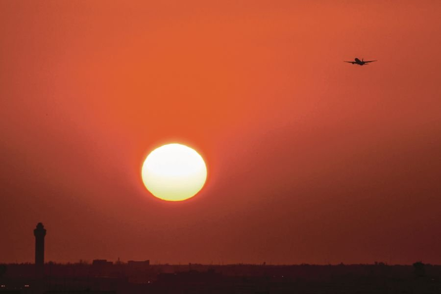 An aeroplane takes off as the sun sets in Miami recently. Progress towards the SDGs is not a linear process, but there is an emerging basis for acceleration in the coming years. -AFP pic