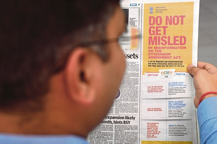 A man reading an advertisement by India's government clarifying facts regarding the Citizenship (Amendment) Act in a newspaper in New Delhi recently. Protests against the act have highlighted the vibrant democratic processes exercised by the diverse Indian population, especially the younger learned generation. - AFP