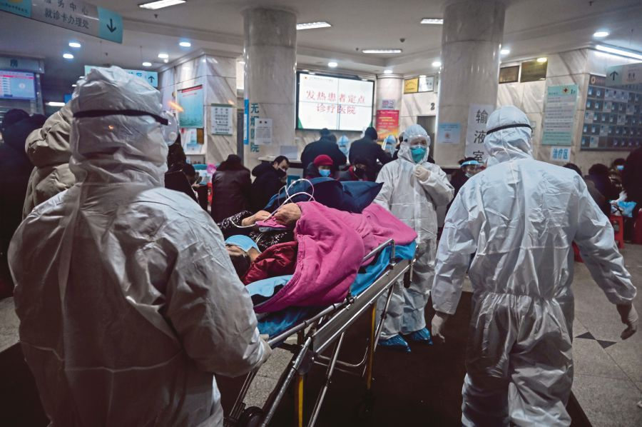 Medical staff wearing protective clothing arriving with a patient at the Wuhan Red Cross Hospital in Wuhan on Saturday. AFP PIC