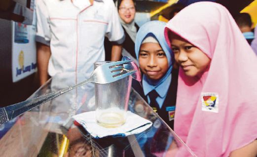 Pupils engrossed in a scientific experiment. — Cover picture courtesy of PINTAR Foundation.