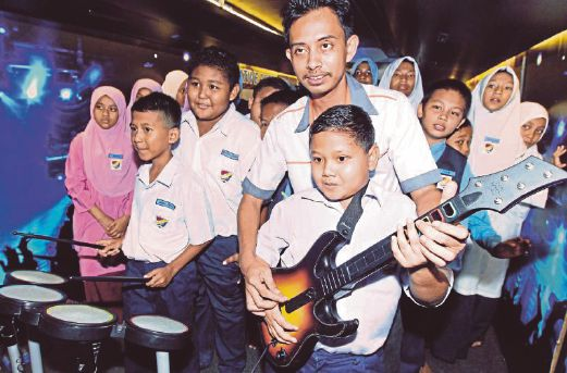 Khairul Anas Shafei shows Year Six pupil Khalish Naqiuddin how to strum a guitar at the performing arts station.