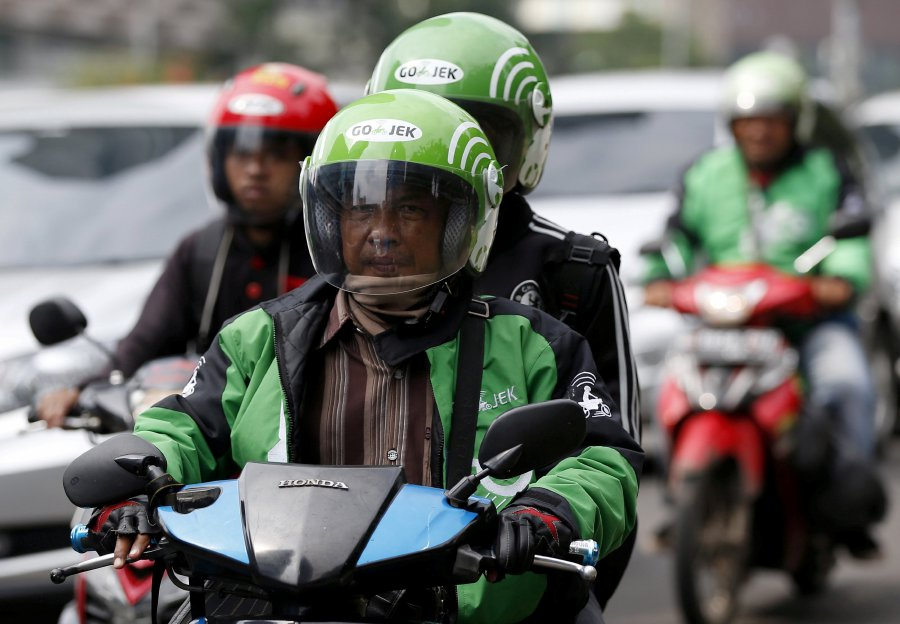 (File pix) A driver and passenger ride on a motorbike, part of the Go-Jek ride-hailing service, on a busy street in central Jakarta, Indonesia December 18, 2015. Reuters Photo