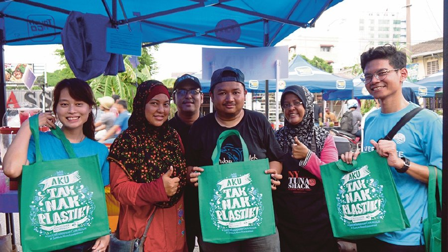 Luqman Avicenna (right) promoting the reduction of plastic use with a tote bag he designed for the River of Life Programme.