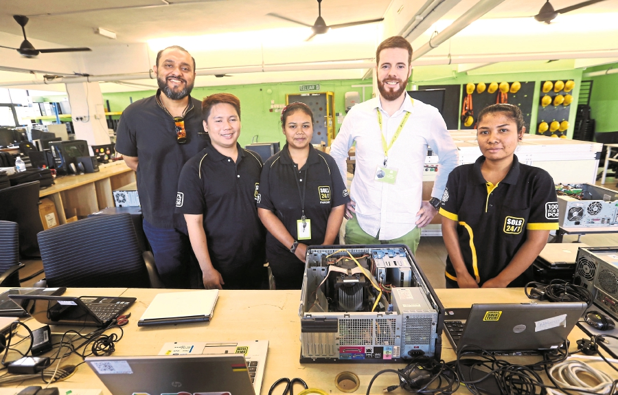 Raj (left) and Alberto Garcia (fourth from left) with employees of SOLS Tech.