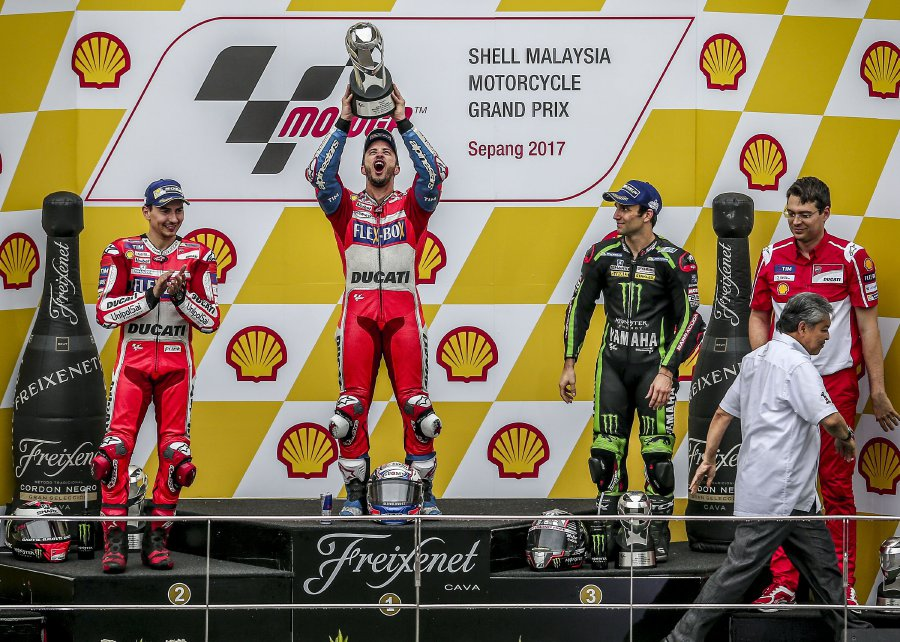 Motorcycling-Dovizioso wins in wet Malaysia to keep title race alive