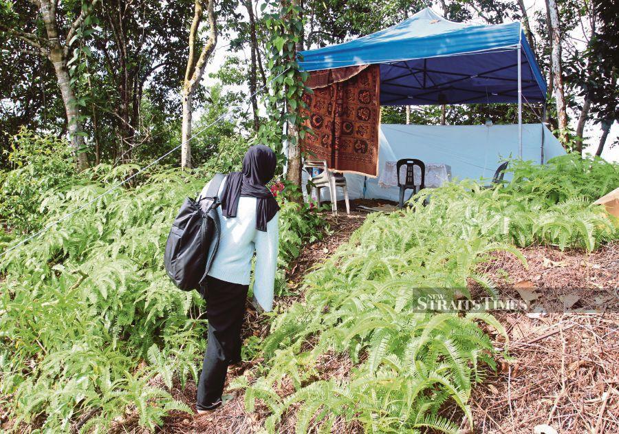 Nurlieda Khaleeda Mohd Azmi climbing up the hill behind her house in Tanah Merah, Kelantan,  yesterday to get a better Internet connection. -- NSTP/ NIK ABDULLAH NIK OMAR