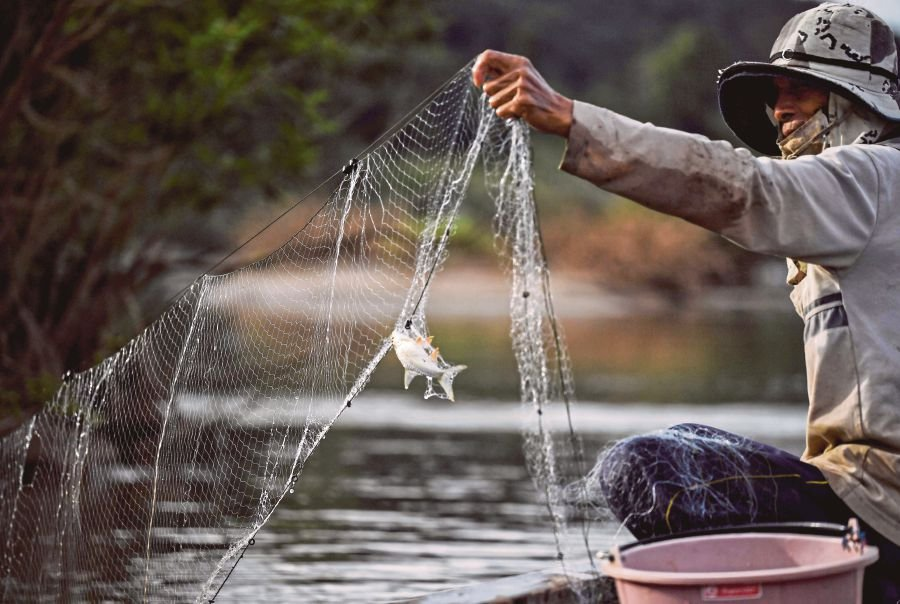 A fisherman checking his net in the Mekong River, Nong Khai district, Thailand. Tourism and fisheries are vital  for livelihoods in the Asia Pacific.  AFP PIC