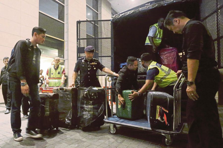 Policemen loading a truck with items seized from Pavilion Residences in Kuala Lumpur last year. The government's stand in taking former prime minister Datuk Seri Najib Razak to court over abuses related to the 1Malaysia Development Bhd scandal is crucial in improving the country's reputation. FILE PIC