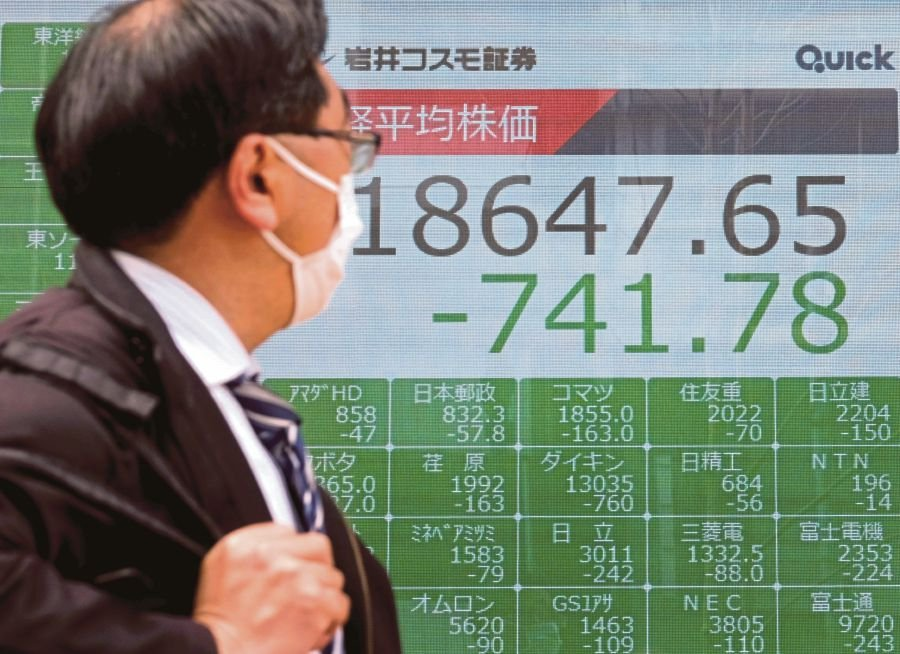 A man wearing a face mask walking past a quotation board displaying share prices of the Tokyo Stock Exchange in Tokyo yesterday. -AFP pic