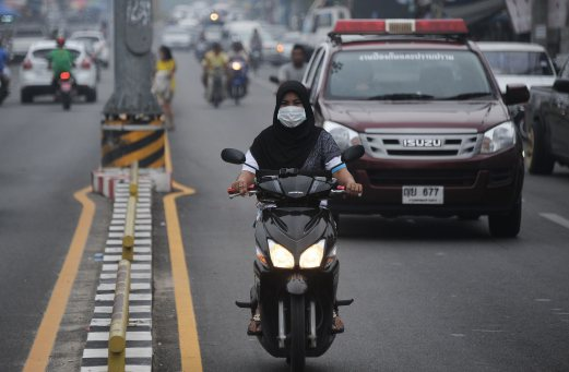 Haze people in southern thailand send letter of complaint to this picture taken on october 5 2015 shows a woman wearing a face mask as she rides a motorcycle through haze in narathiwat southern thailand spiritdancerdesigns Gallery