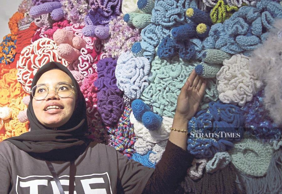 Universiti Teknologi Mara textile design student Liana Muhamed Ismadi showcasing her fiber art wall of coral reefs at the Textile Eco Exploration and Experimental Design (TEEED) 2020 show in Kuala Lumpur recently. - NSTP/Nik Hariff Hassan