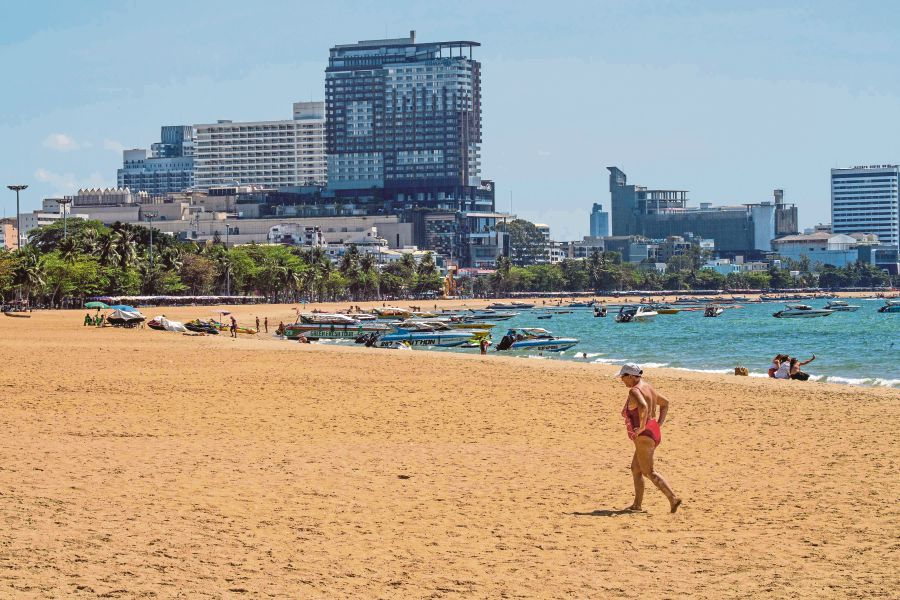 A tourist strolling along a beach nearly devoid of tourists in Pattaya, Thailand, on Saturday. The number of visitors coming to the region has plunged due to the Covid-19 outbreak. -AFP pic