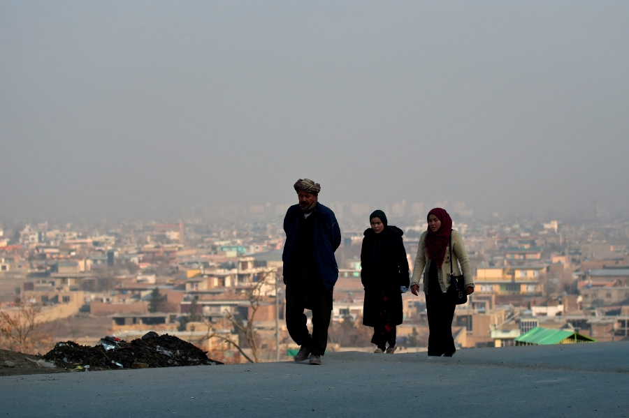 A man walks along with women on a hillside overlooking Kabul on February 22, 2020. - A week-long partial truce took hold across Afghanistan on February 22, with some jubilant civilians dancing in the streets as the war-weary country woke up to what is potentially a major turning point in its long conflict. (Photo by WAKIL KOHSAR / AFP)