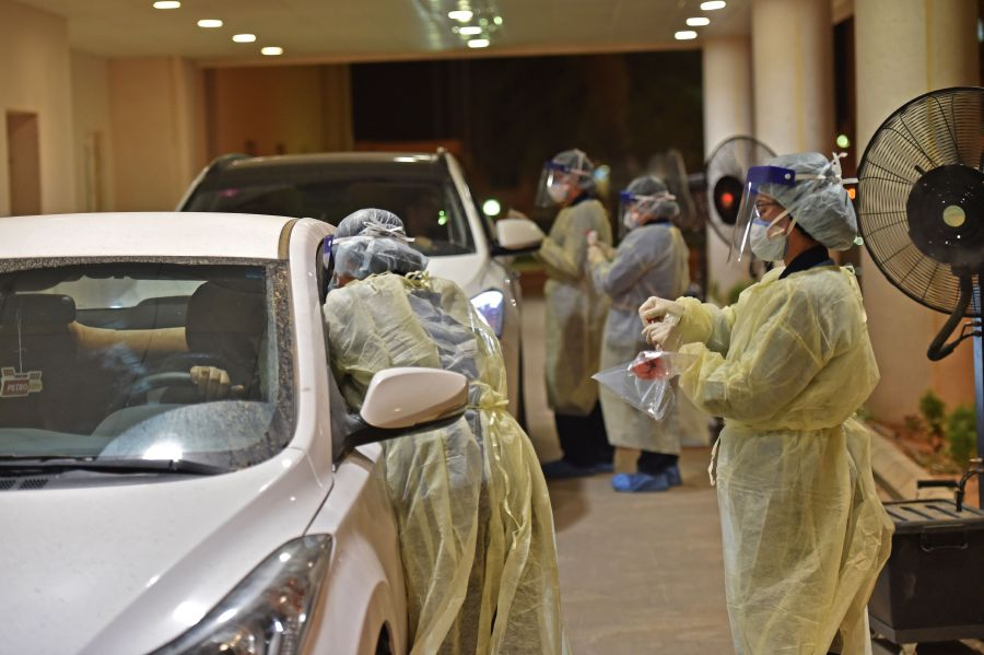Health workers perform a nose swab test during a drive through coronavirus test campaign held in Diriyah hospital in the Saudi capital Riyadh amid the COVID-19 pandemic. (Photo by FAYEZ NURELDINE / AFP)