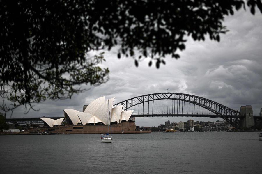 A boat sails in front of the Opera House in Sydney on December 30, 2020, as authorities work to suppress a growing cluster of Covid-19 coronavirus cases in Australia's most populous city. (Photo by Saeed KHAN / AFP)