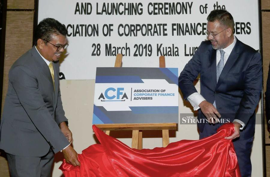Bursa Malaysia Bhd chief executive officer Datuk Muhamad Umar Swift (right) and ACFA chairman Datuk Wan Asmadi Wan Ahmad (left) at the launch of the Association of Corporate Finance Advisers (ACFA) logo. NSTP photo by ROSDAN WAHID