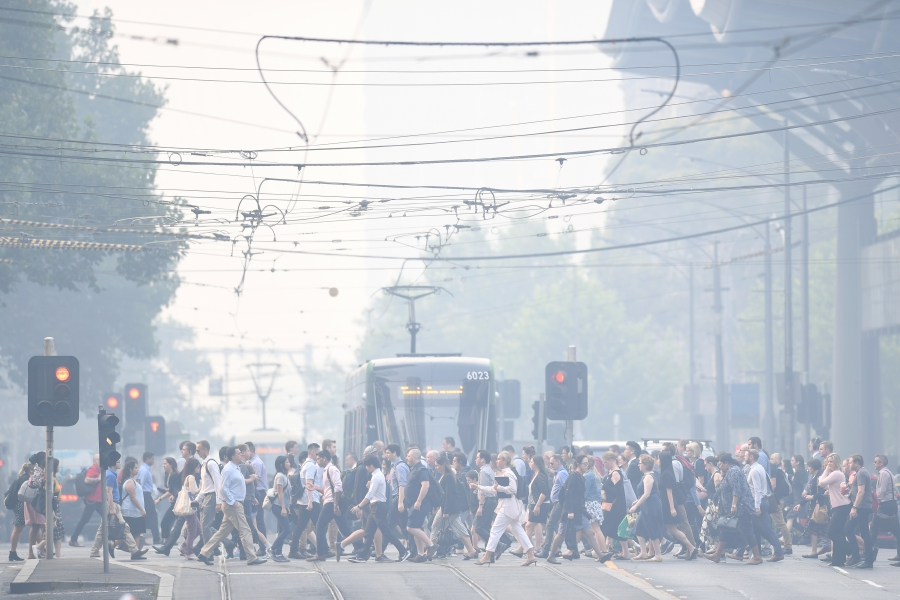 Morning commuters are seen through smoke haze from bushfires in Melbourne Australia