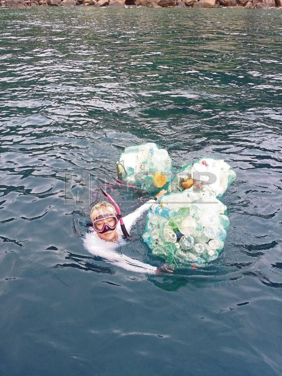 A participant swims back to the boat after collecting trash on Tulai Island