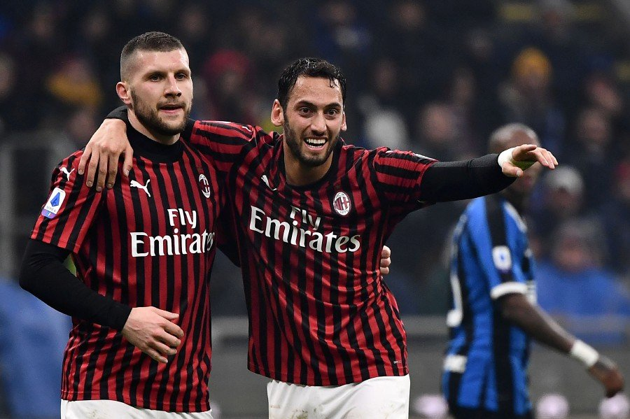AC Milan's forward Ante Rebic (left) celebrates after scoring with his teammate Hakan Calhanoglu during the match against Inter Milan at the San Siro stadium in Milan. - AFP