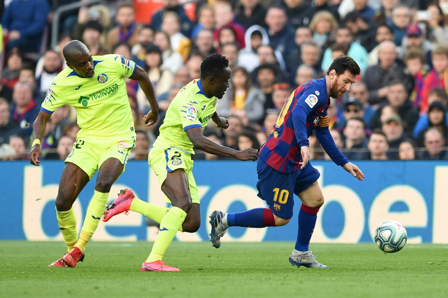 Getafe's Togolese defender Djene (C) and Getafe's Cameroonian defender Allan Nyom (L) challenge Barcelona's Argentine forward Lionel Messi during the Spanish league football match between FC Barcelona and Getafe CF at the Camp Nou stadium in Barcelona on February 15, 2020. (Photo by Josep LAGO / AFP)