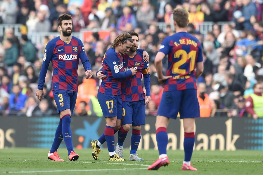 Barcelona's French forward Antoine Griezmann (2L) celebrates with Barcelona's Argentine forward Lionel Messi after scoring during the Spanish league football match between FC Barcelona and Getafe CF at the Camp Nou stadium in Barcelona on February 15, 2020. (Photo by Josep LAGO / AFP)