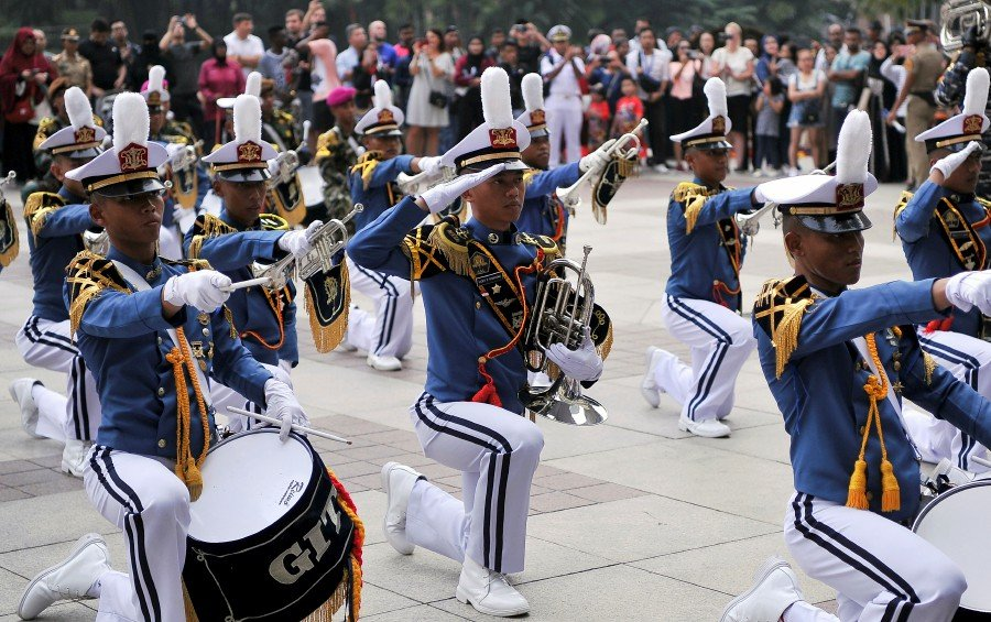 Members of the KRI Bima Suci 945's cadet marching band giving a salute before beginning their performance at Suria KLCC in Kuala Lumpur. Image: Bernama
