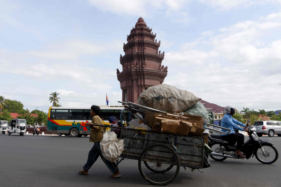 A Cambodian scavenger pulls her cart loaded with the recyclable materials pass the Independence monument in Phnom Penh on October 17, 2019.-AFP