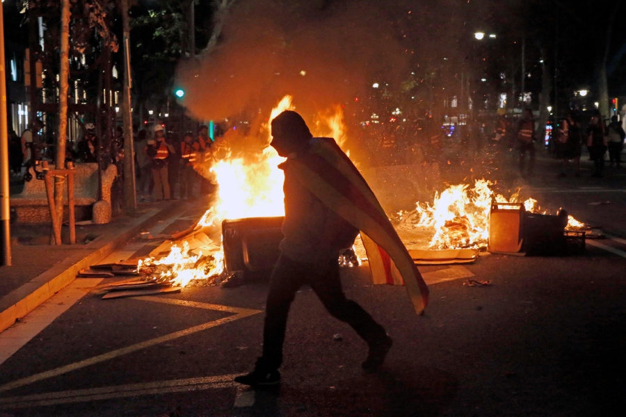 A demonstrator walks near a fire barricade during a protest in Barcelona, Spain, 26 October 2019. Catalonia region in Spain is witnessing massive demonstrations and riots against the Supreme Court ruling of prison terms against the Catalan political leaders accused of organizing the Catalan illegal referendum held in October 2017. EPA/QUIQUE GARCIA
