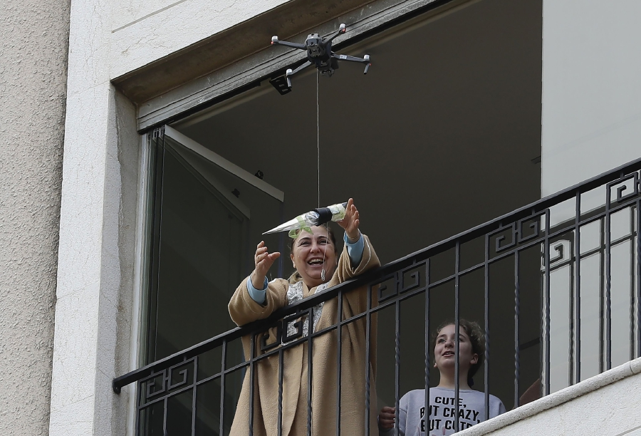 A woman standing on her balcony, reaches out to catch a rose delivered to her via a drone on Mother's day, in the Lebanese coastal city of Jounieh, north of the capital Beirut on March 21, 2020, as people remain indoors in an effort to limit the spread of the novel coronavirus. - Three young Lebanese came up with the idea of delivering roses attached to drones, offered to mothers by their children as a surprise gift. The funds collected from this initiative will be donated to the Lebanese Red Cross to help fight against the CIVID-19 pandemic. (Photo by JOSEPH EID / AFP)