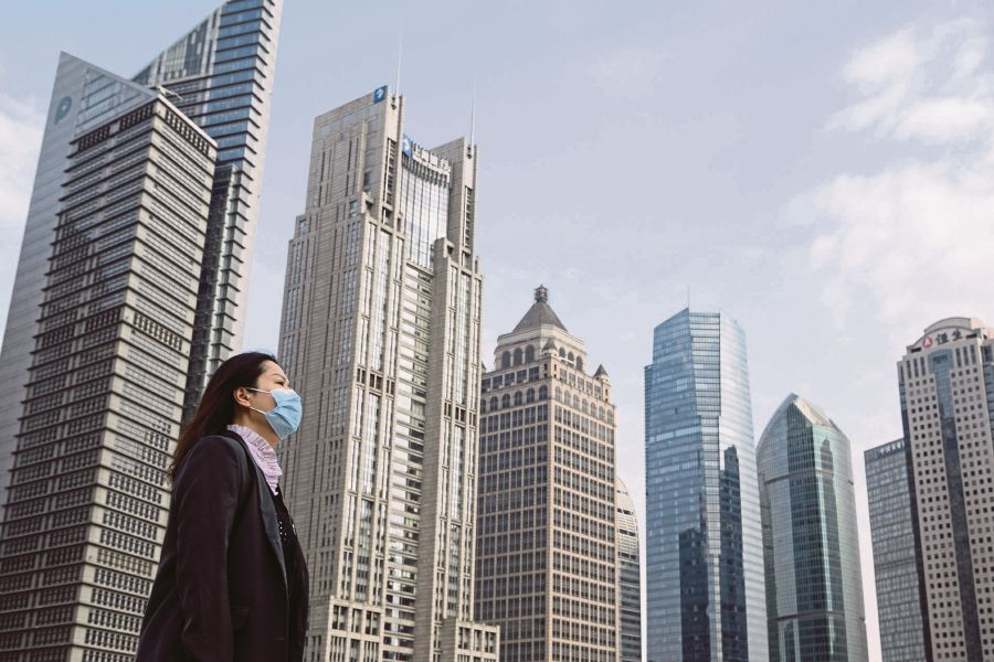 A woman wearing a protective face mask walks on an overpass in Shanghai, China. -AFP