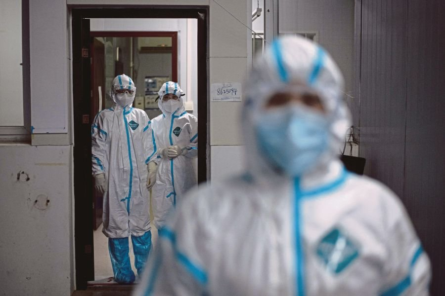 Medical workers wearing hazmat suits as a preventive measure against the COVID-19 coronavirus are seen at a fever clinic in Huanggang Zhongxin Hospital in Huanggang, in China�s central Hubei province. -AFP pic