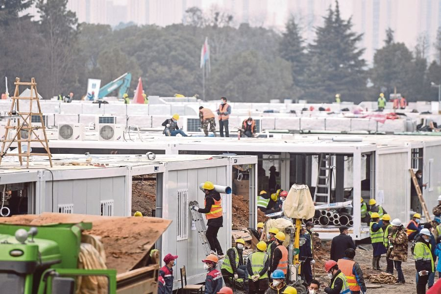 "Chinese employees work at the construction site of the Huoshenshan hospital, which means ""Fire God Mountain"", before handed over to China's army in Wuhan in China's central Hubei province on February 2, 2020. - China's army on February 2 was given control of a nearly-finished field hospital that will treat patients at the epicentre of a deadly virus epidemic that has severely strained medical facilities. AFP"