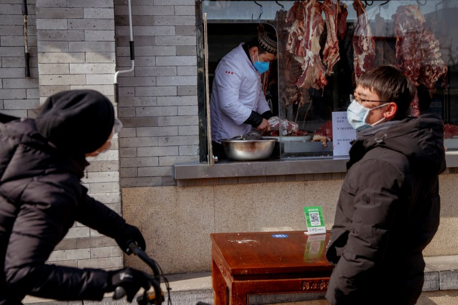People wearing face masks buy meat from a butcher after the novel coronavirus outbreak in Beijing, China, February 23, 2020. - REUTERS/Thomas Peter