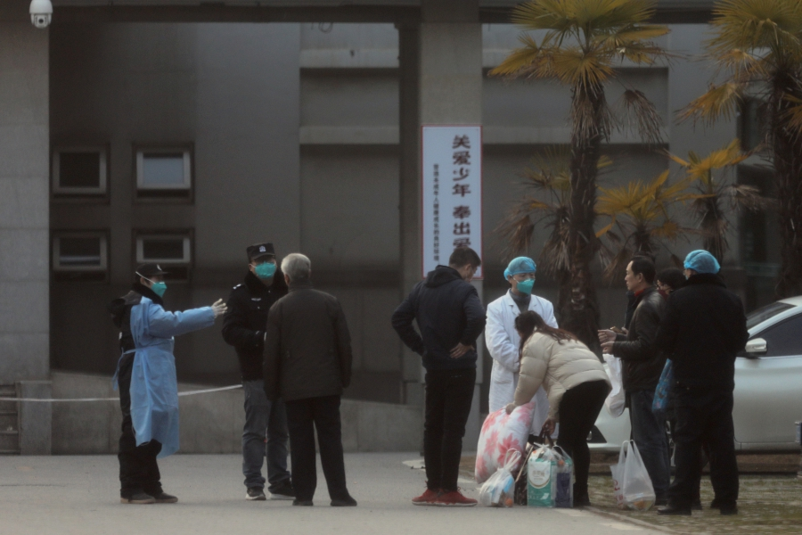 FILE PHOTO: Medical staff and security personnel stop patients' family members from being too close to the Jinyintan hospital, where the patients with pneumonia caused by the new strain of coronavirus are being treated, in Wuhan, Hubei province, China January 20, 2020. REUTERS/Stringer/File Photo