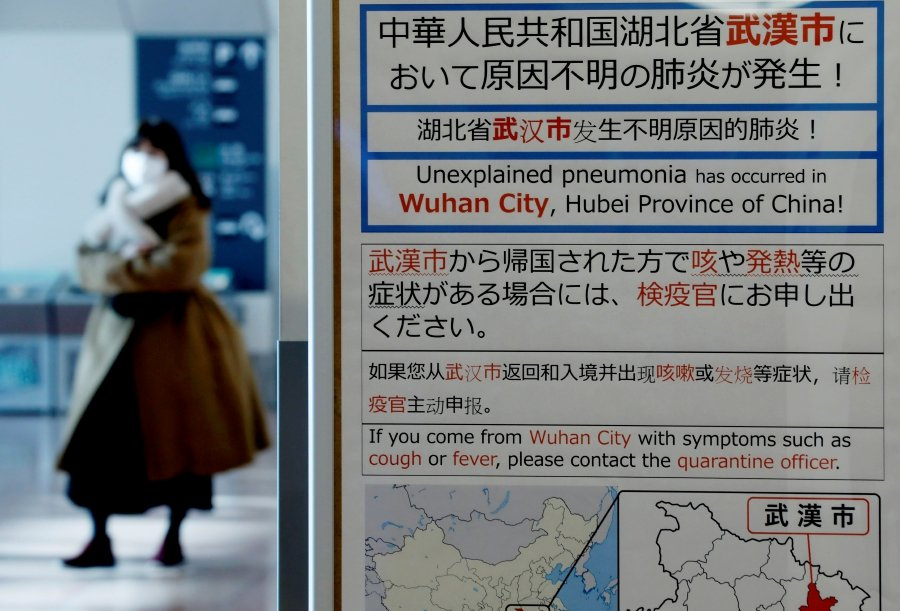 A woman wearing a mask walks past a quarantine notice about the outbreak of coronavirus in Wuhan, China at an arrival hall of Haneda airport in Tokyo, Japan. -REUTERS