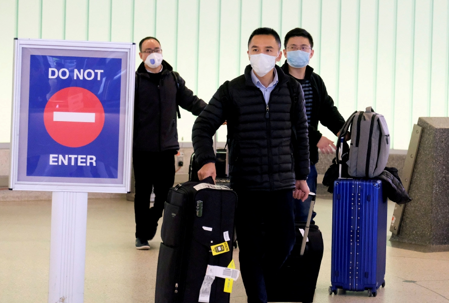 FILE PHOTO: Passengers arrive at LAX from Shanghai, China, after a positive case of the coronavirus was announced in the Orange County suburb of Los Angeles, California, U.S. - REUTERS/Ringo Chiu/File Photo